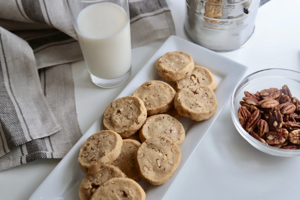 Salted Pecan Brown Sugar Cookies on a plate with glass of milk