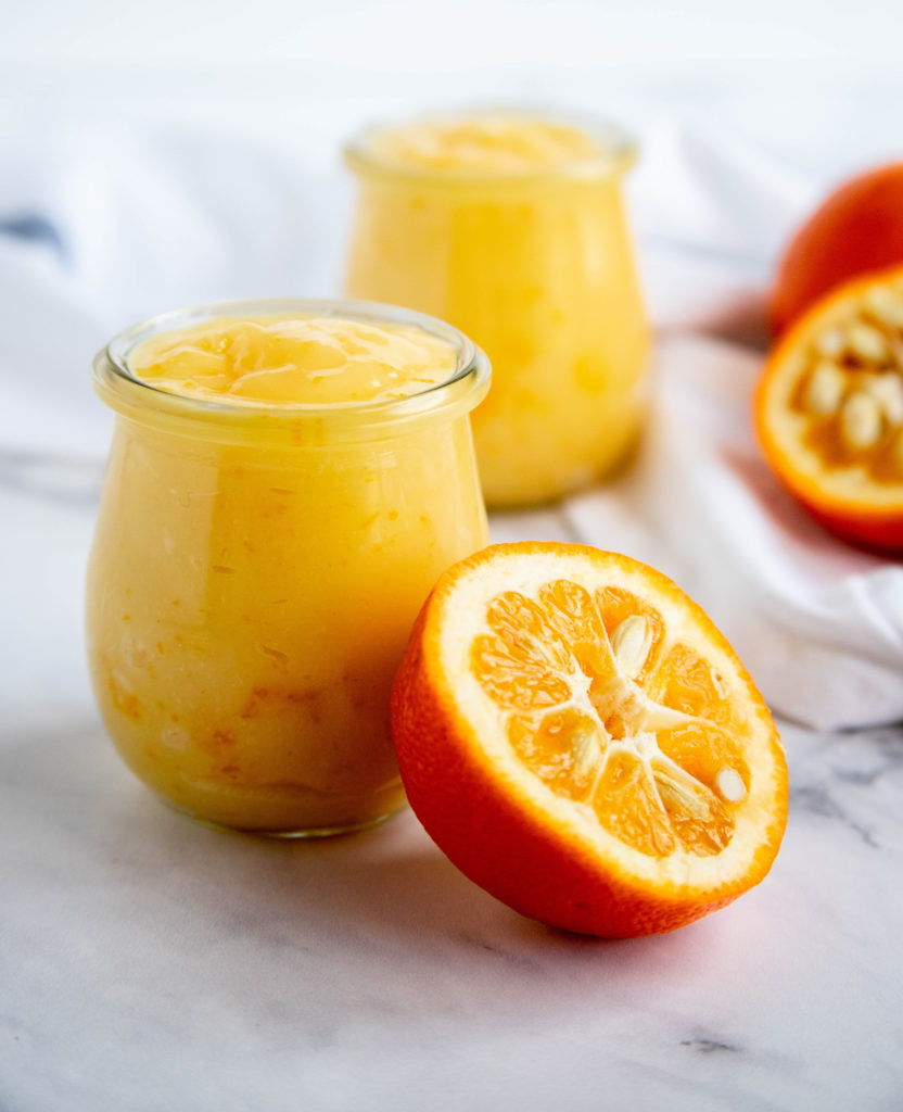Seville Orange Curd in a jar with fresh Seville Oranges