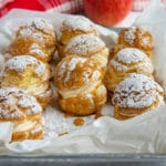9 Apple Filled Cream Puffs with Caramel Sauce and sprinkled with powdered sugar arranged on parchment paper