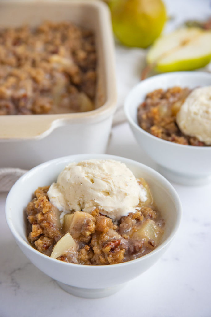 Pear Crisp in a white bowl and topped with a scoop of vanilla ice cream.
