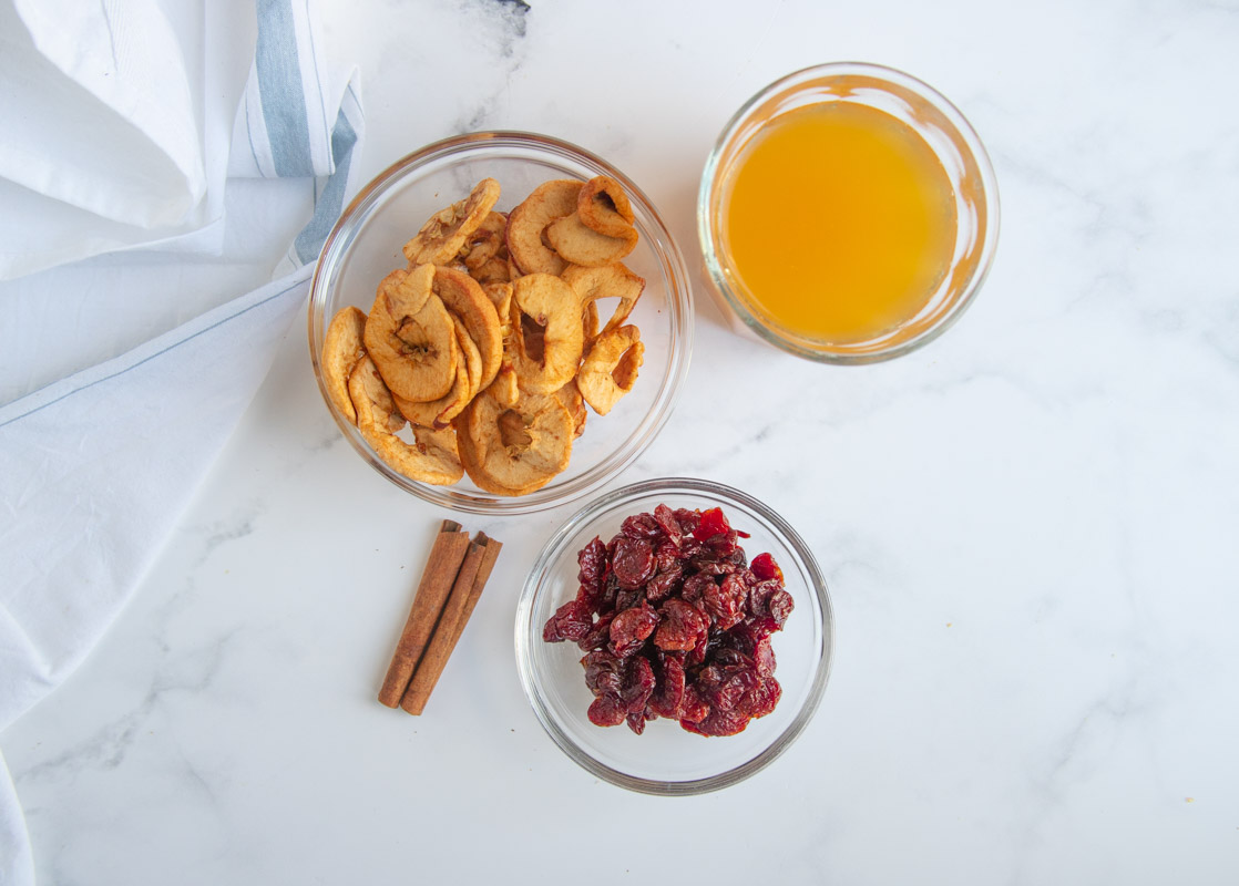 Dried apples, apple cider and dried cherries in separate bowls