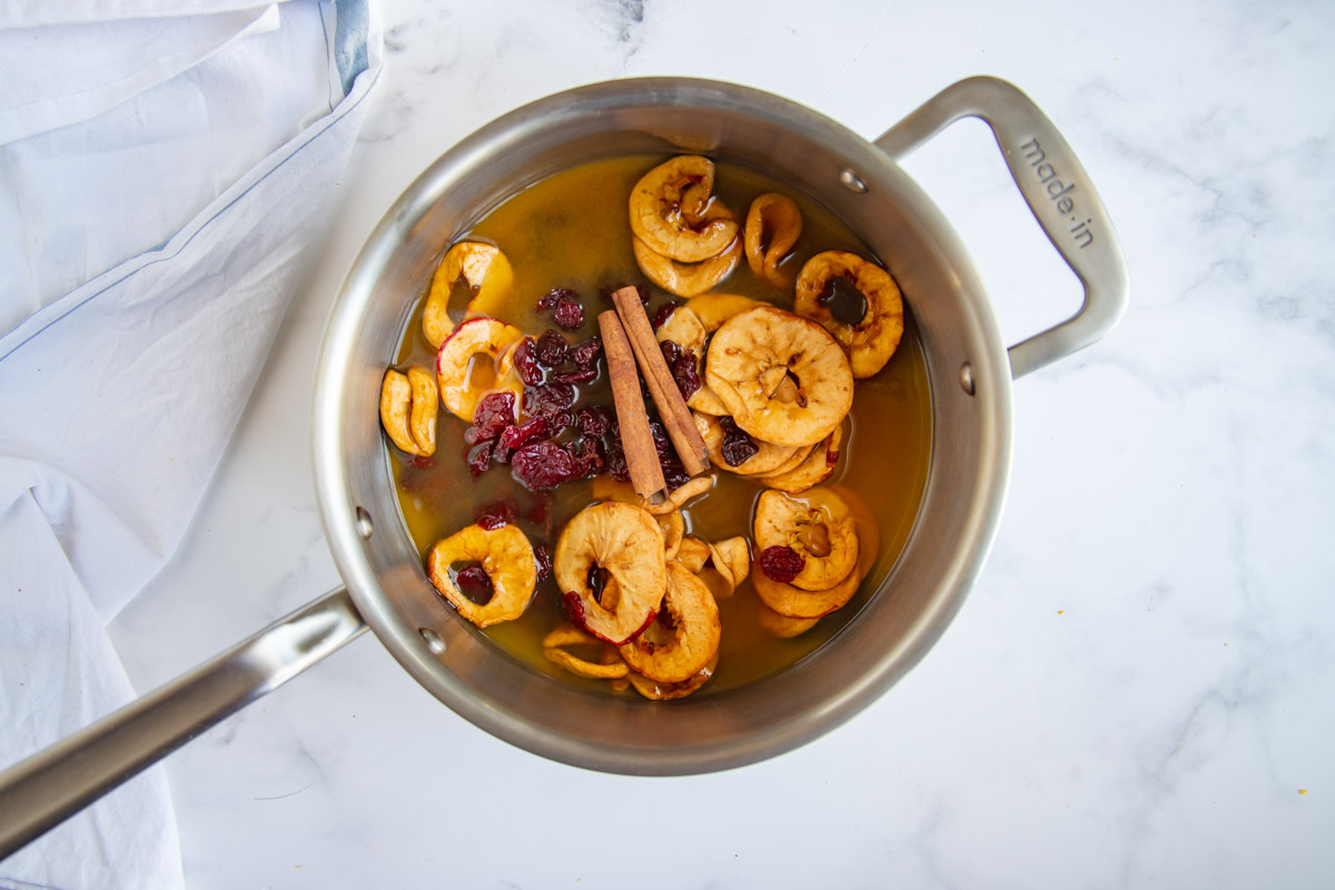 Dried apples, dried cherries, cinnamon and apple cider in a saucepan