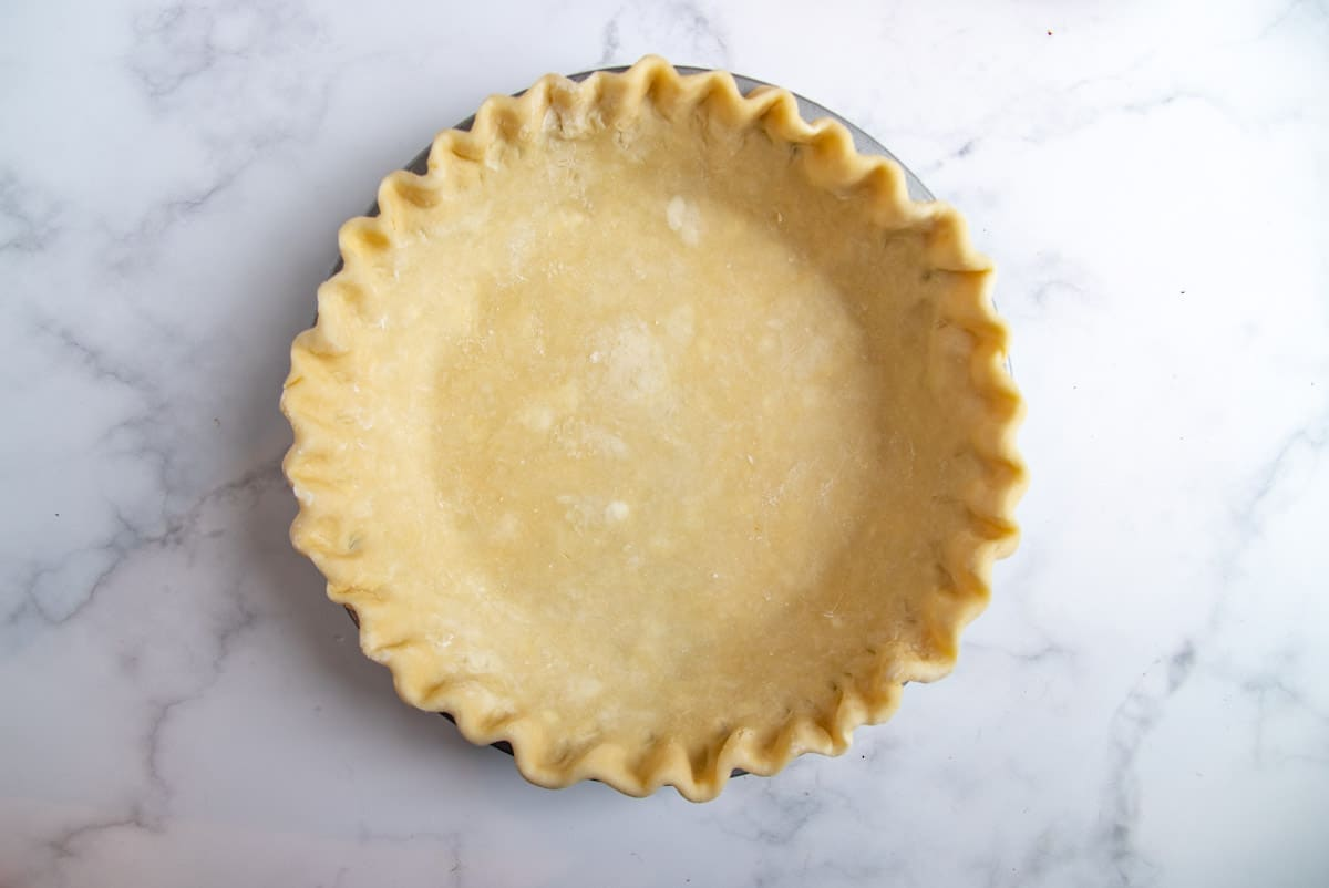 pie dough in the pie plate with crimped edges