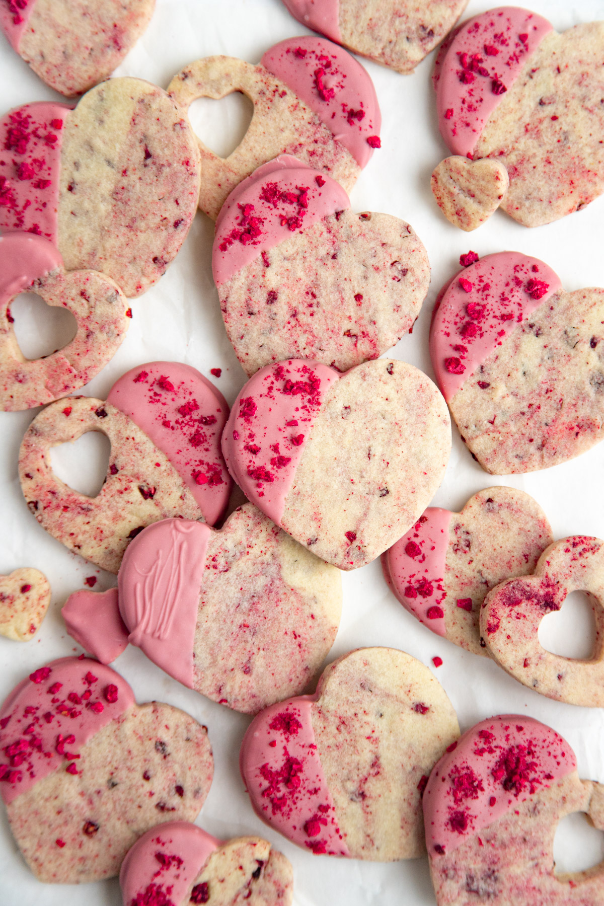 Raspberry heart-shaped shortbread cookies with ruby chocolate glaze