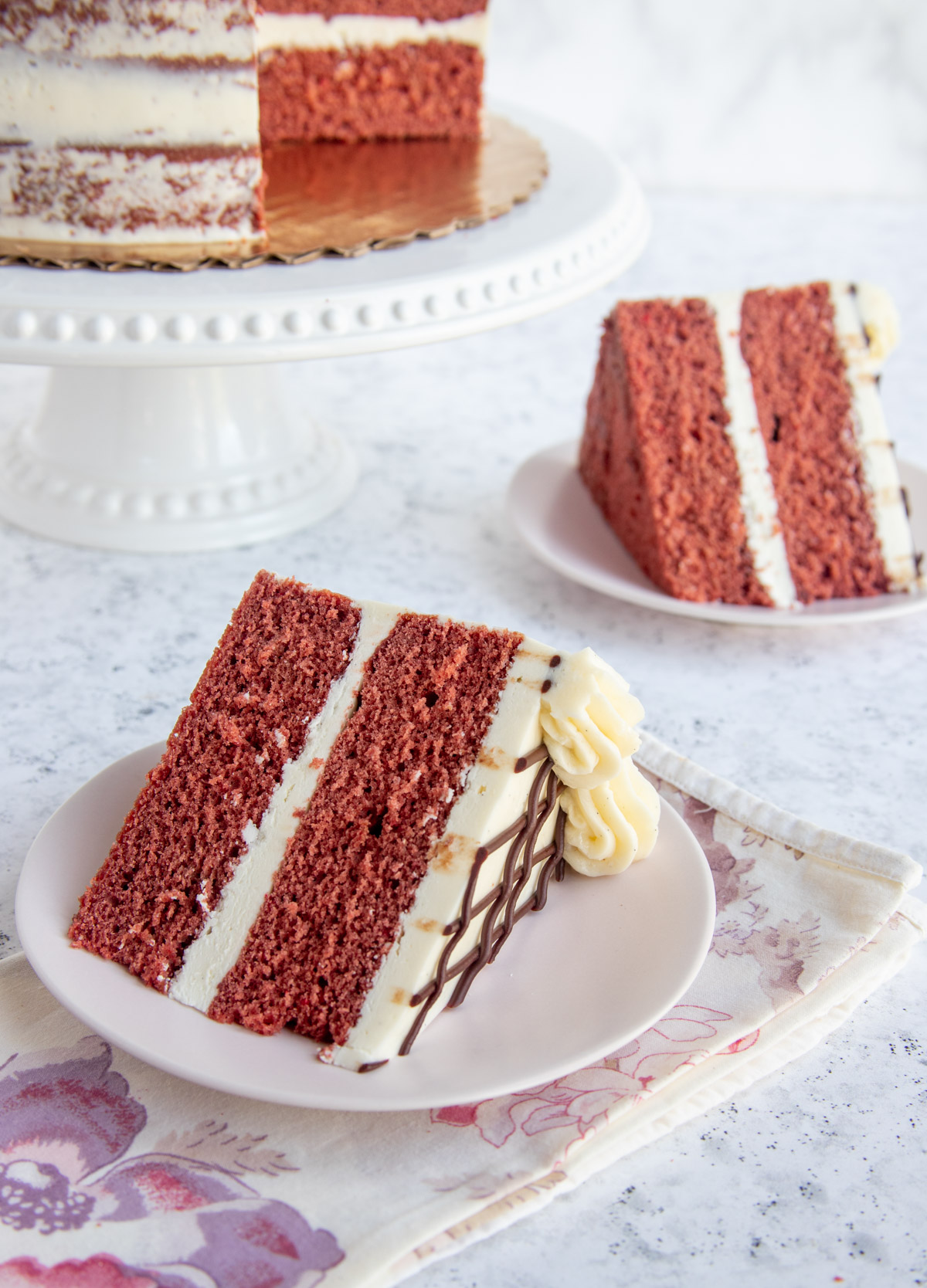 Red Velvet Cake with Mascarpone Buttercream - two slices on two small plates and the main cake in the background on a cake plate.