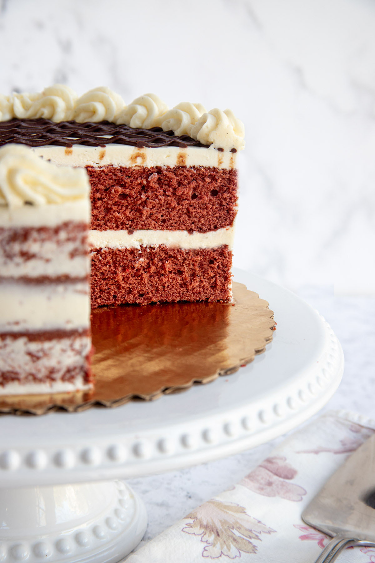 A cut Red Velvet Cake with mascarpone buttercream on a cake plate