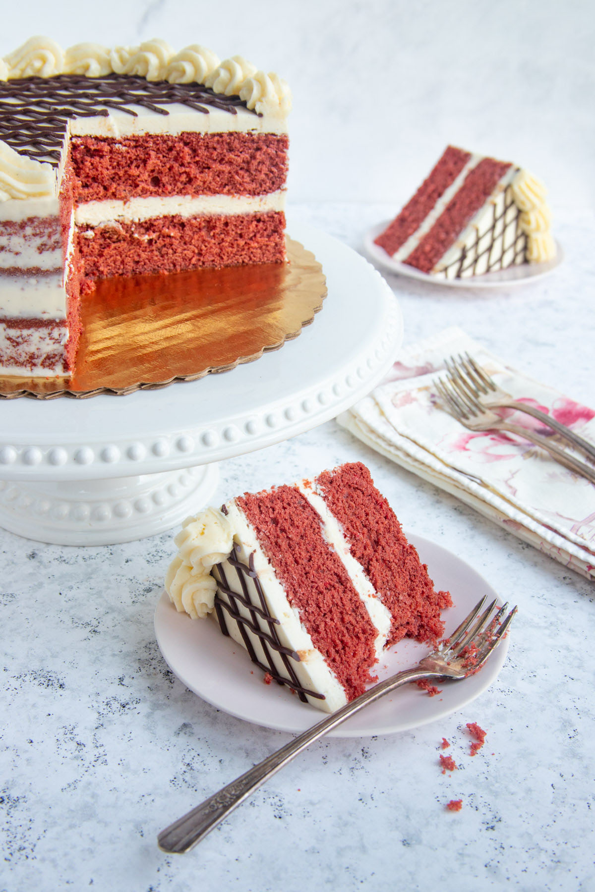 Red Velvet Cake with Mascarpone Buttercream - two slices on two small plates and the main cake on a cake stand