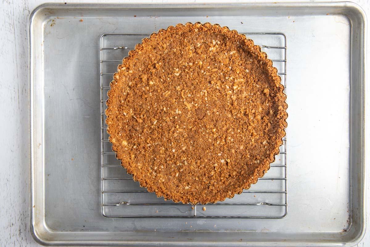 Ginger cookie crust on racking sitting on baking sheet before baking it