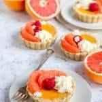 Grapefruit curd mini tarts decorated with whipped cream, fresh grapefruit and fresh raspberries. Fresh cut grapefruit sit next to the tarts