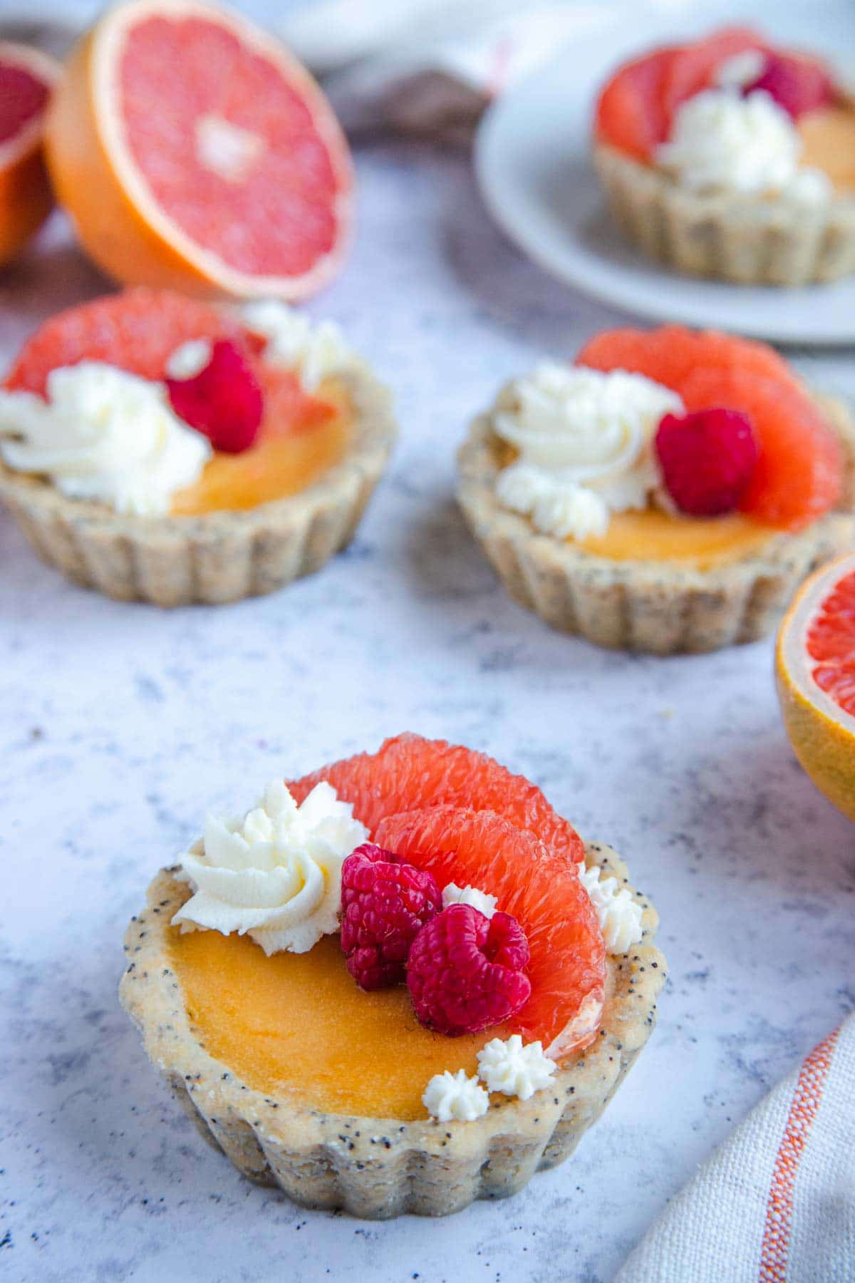 Grapefruit curd mini tarts decorated with whipped cream, fresh grapefruit and fresh raspberries.  Fresh cut grapefruit sit next to the tarts