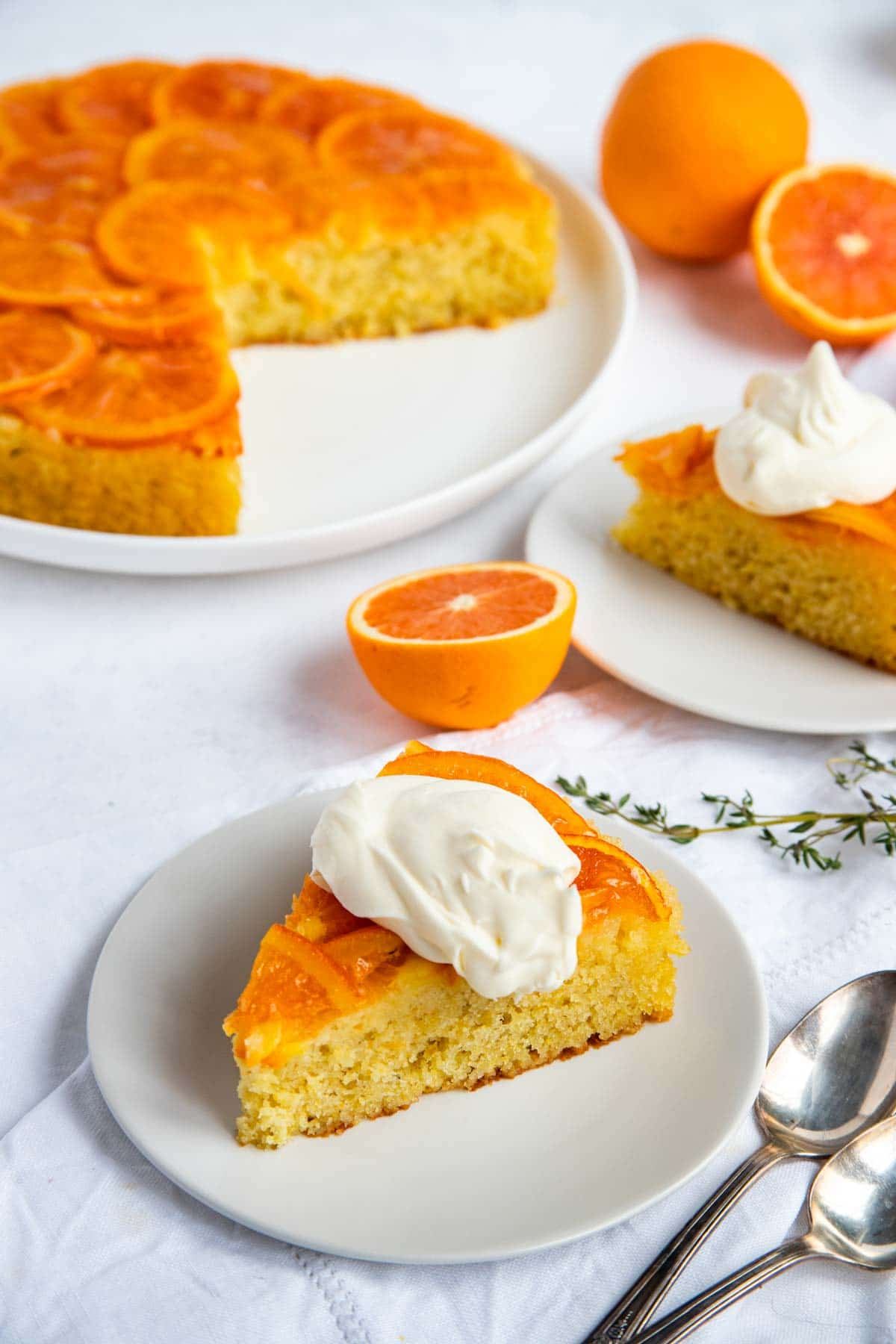 Orange upside-down cake on a plate surrounded by whole and cut oranges and two slices of cake on dessert plates with whipped creme fraiche