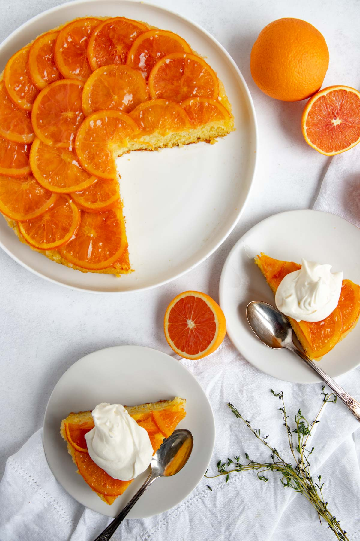 Orange upside-down cake on a plate surrounded by whole and cut oranges and two slices of cake on dessert plates