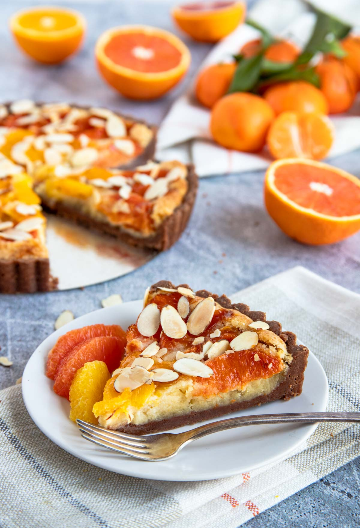 A slice of the orange and chocolate almond tart with fresh cut oranges and the tart in the background