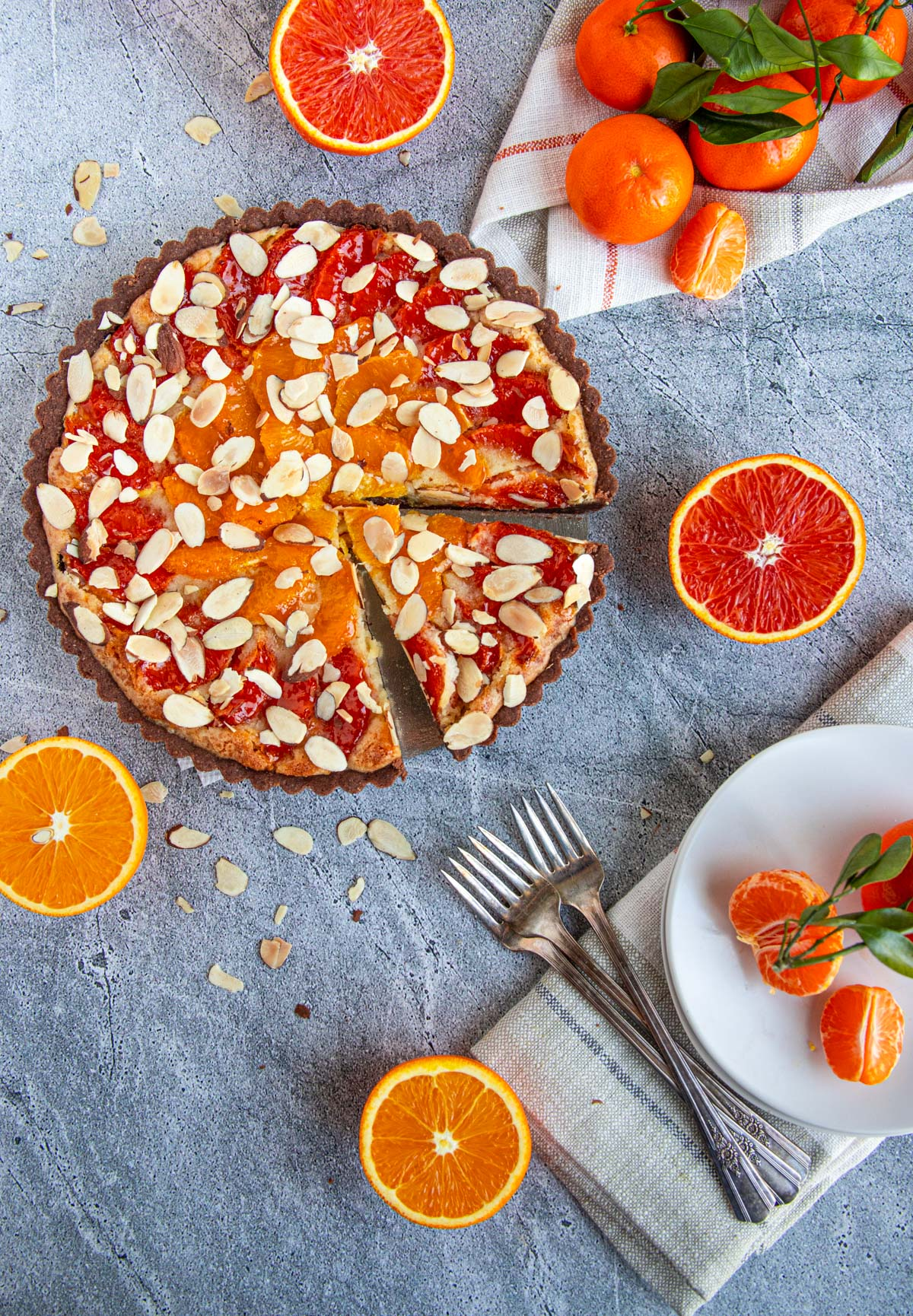 Orange and Chocolate Almond Tart with fresh cut oranges, forks and dessert plates