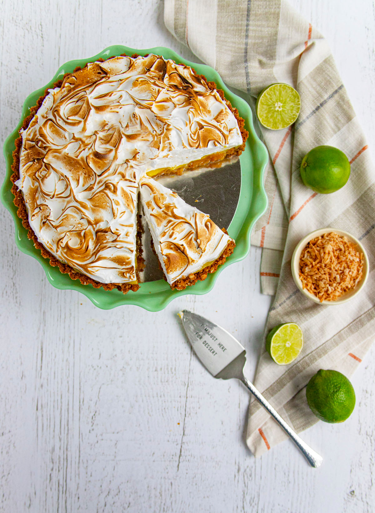 Roasted Pineapple and Lime Curd Tart on a green cake stand with limes in the background