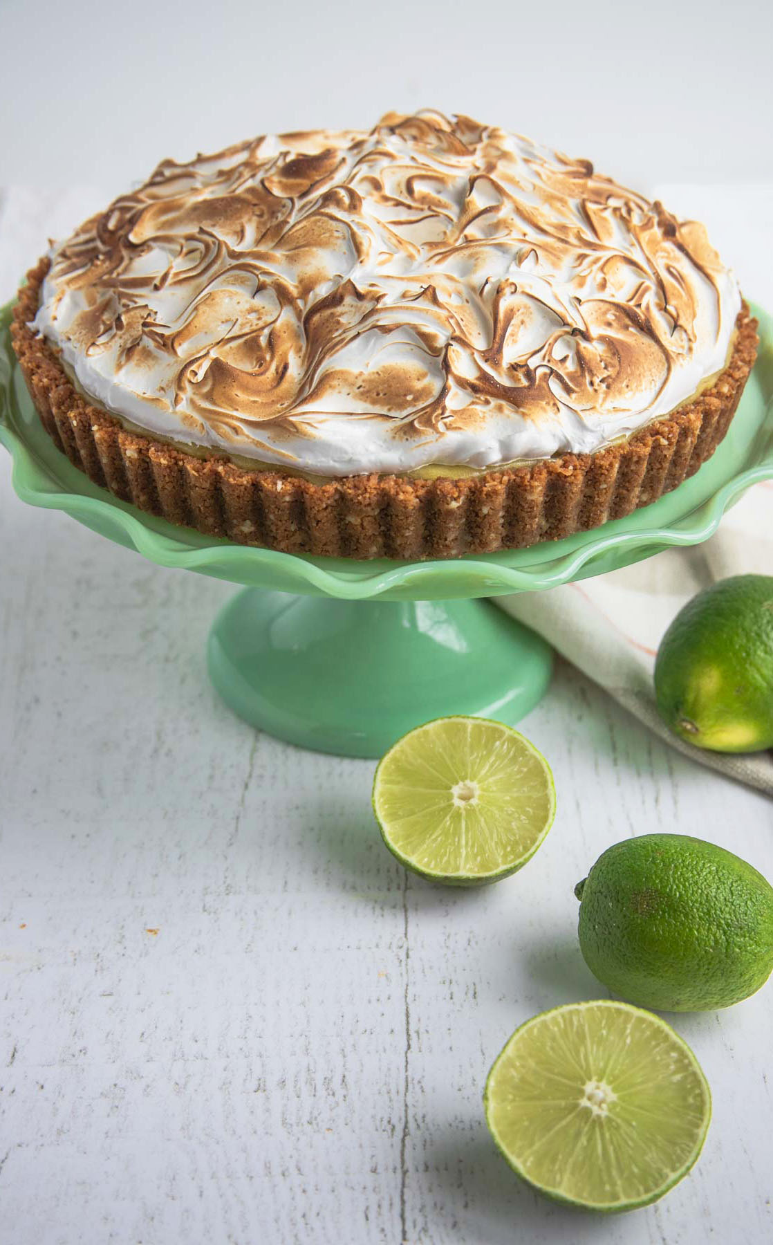 Roasted Pineapple and Lime Curd Tart on a green cake stand with limes in the foreground
