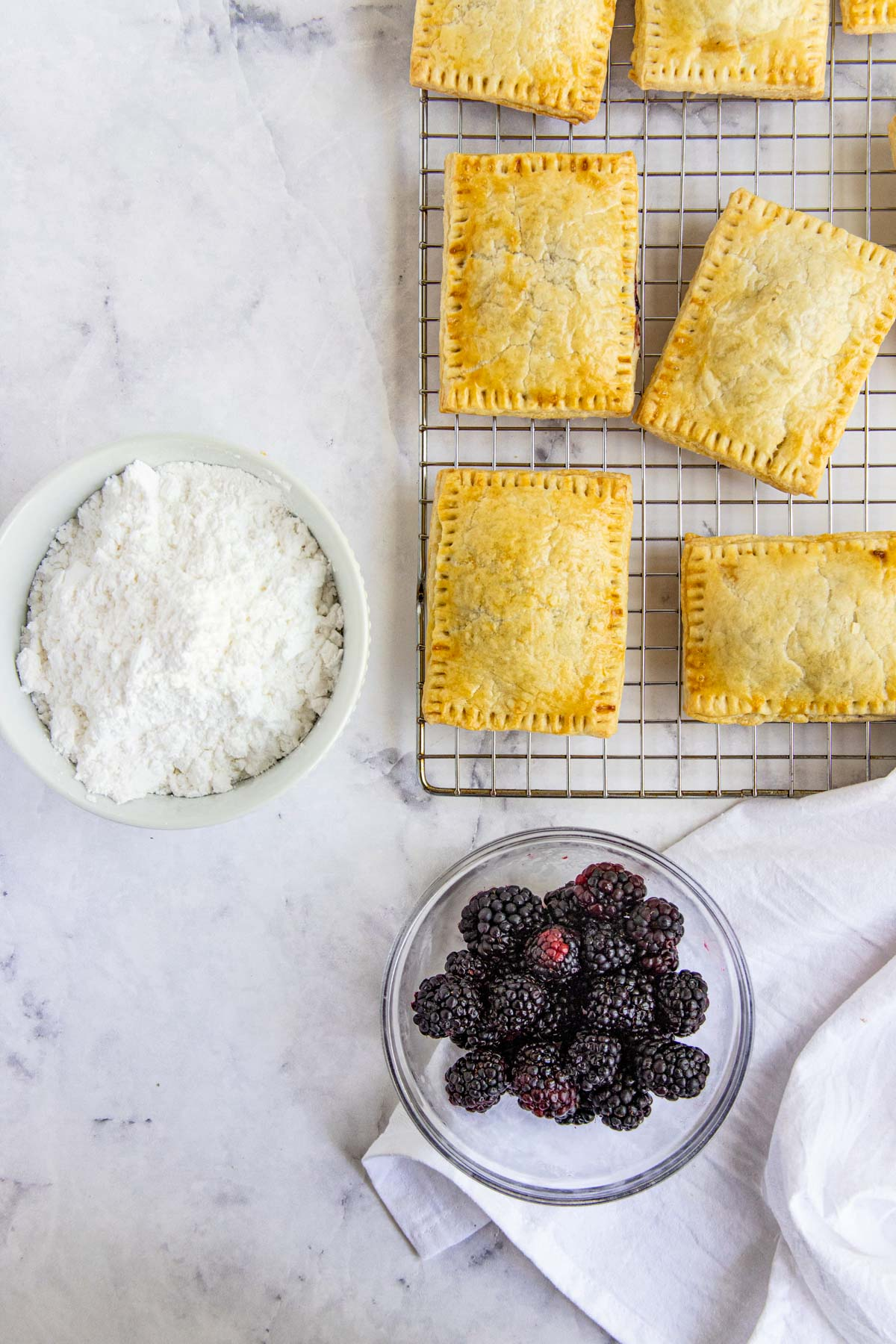 Baked blackberry hand pies  on a cooling rack with bowls of powdered sugar and fresh raspberries next to the pies.