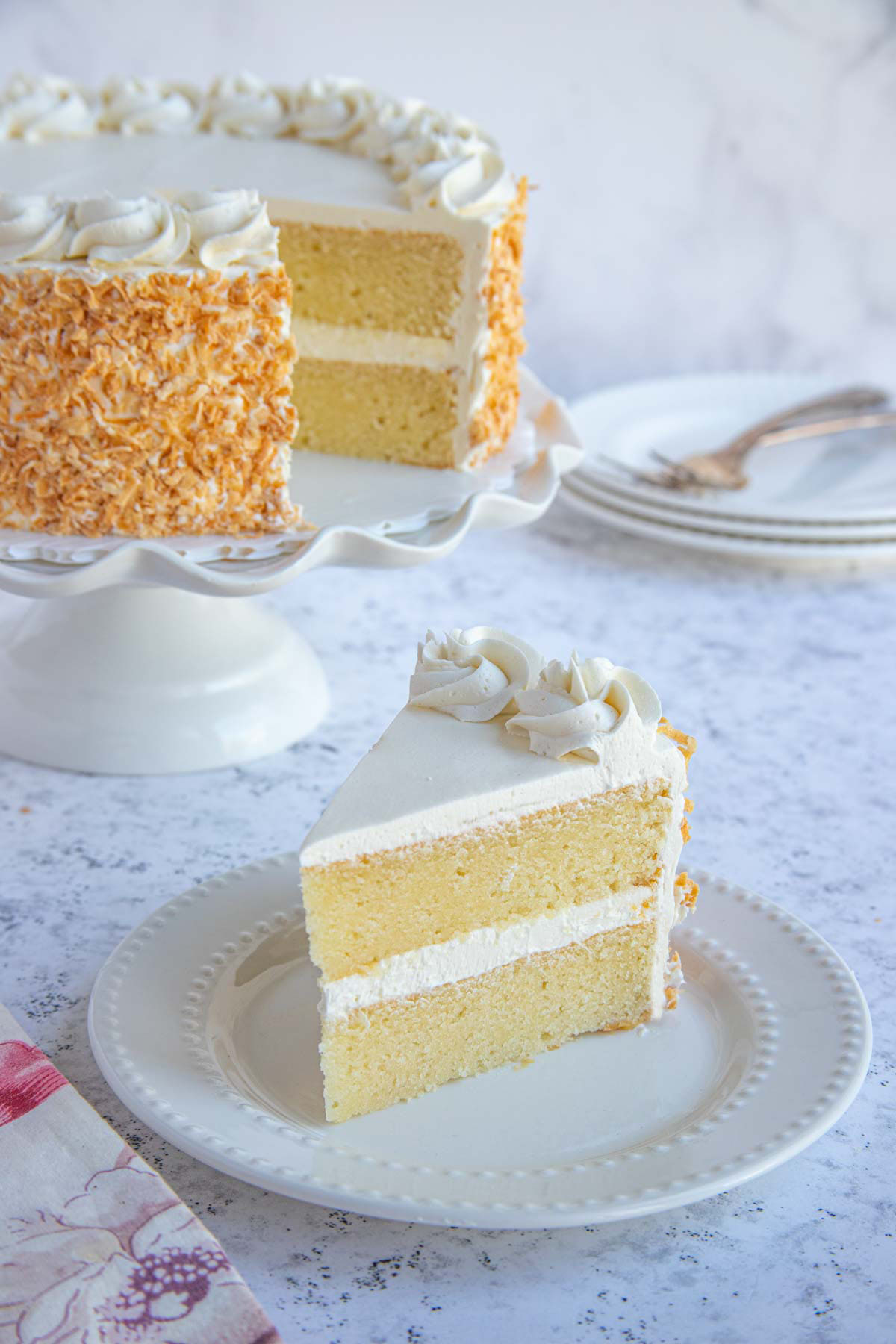 Coconut Layer Cake with Toasted Coconut Frosting on cake stand.  A cake slice on a white plate is in front of the cake