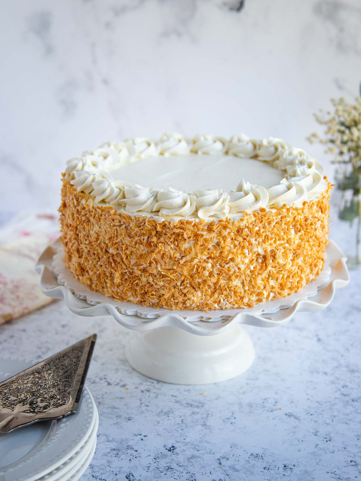 Coconut Layer Cake with Toasted Coconut Frosting on cake stand.  Cake server and cloth napkins on the left of the cake stand.