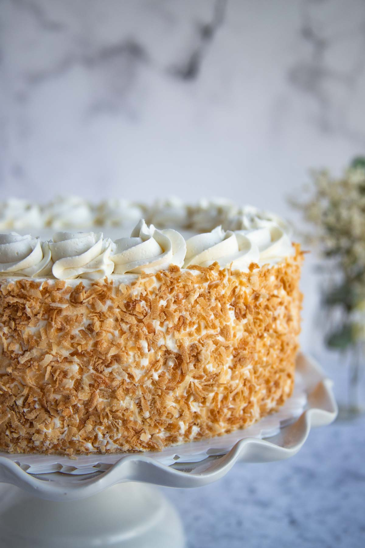 Coconut Cake with toasted coconut coating on a cake stand.  Flowers in the background.