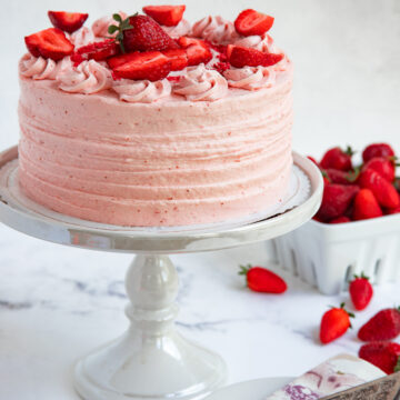 Fresh Strawberry Cake on a cake stand next to a basket of fresh strawberries