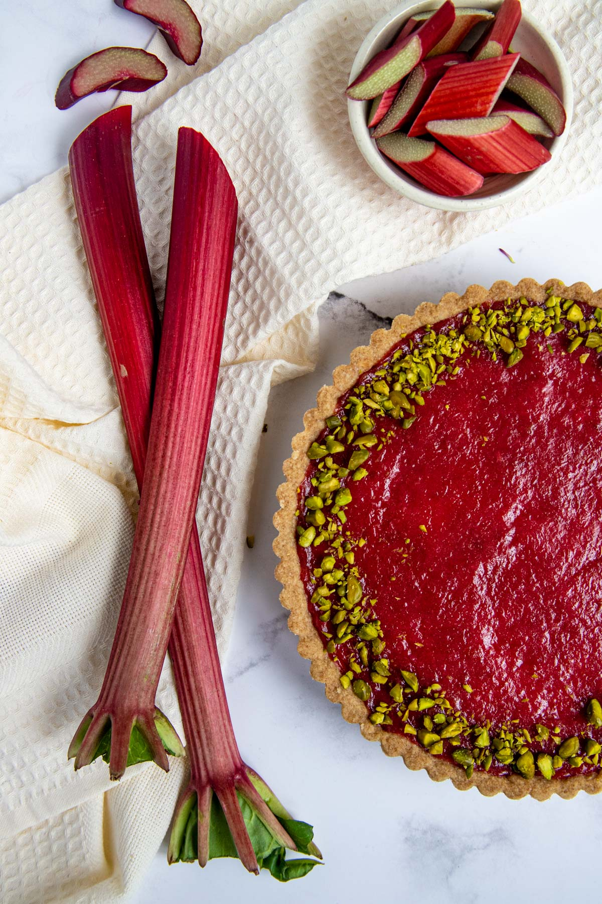 Rhubarb cream tart with stalks of rhubarb and chopped rhubarb next to the tart. The rhubarb tart is sprinkled wi