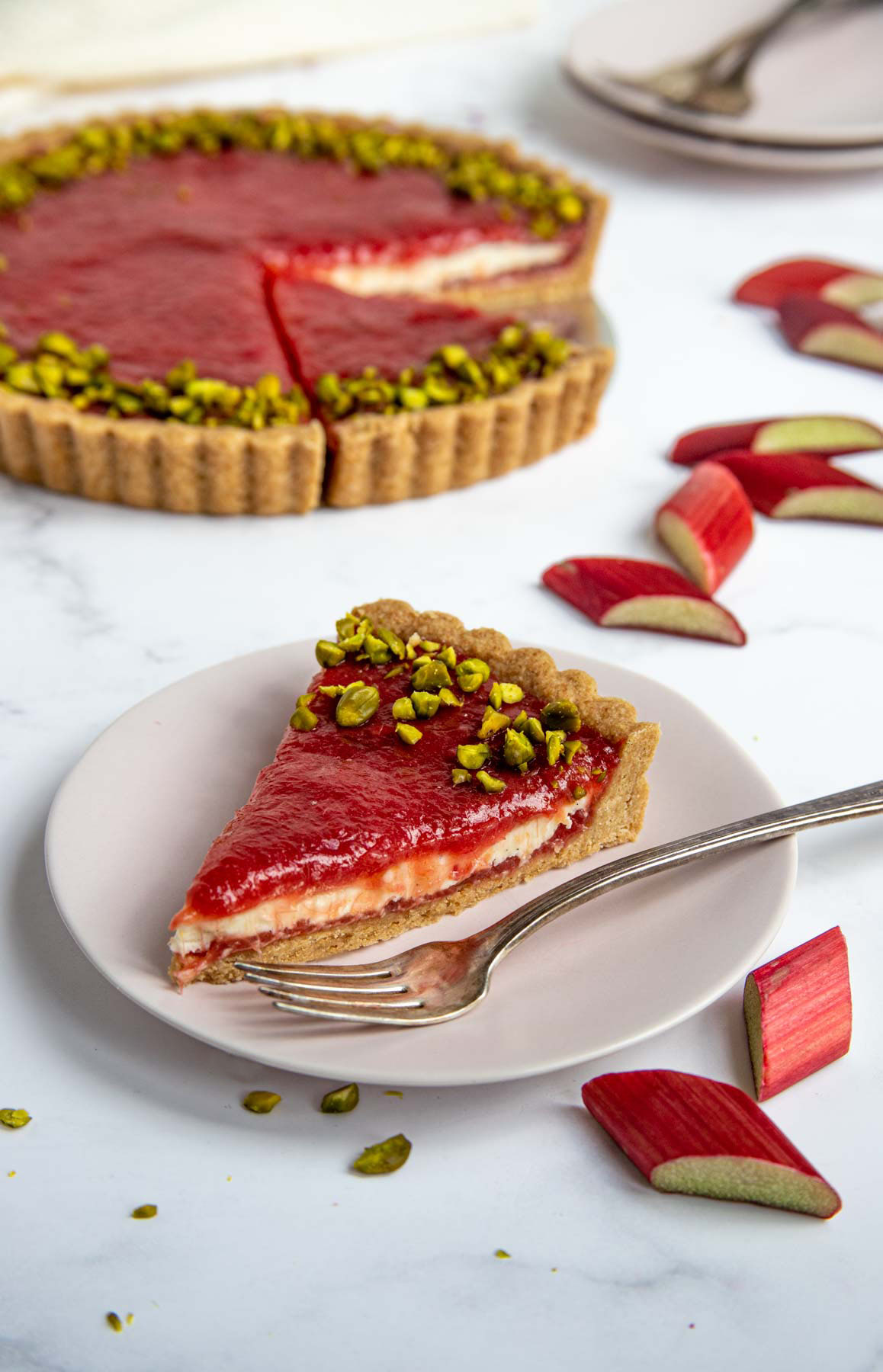 A slice of the rhubarb cream tart on a pink dessert plate with the tart in with chopped rhubarb and the rhubarb tart in the background.