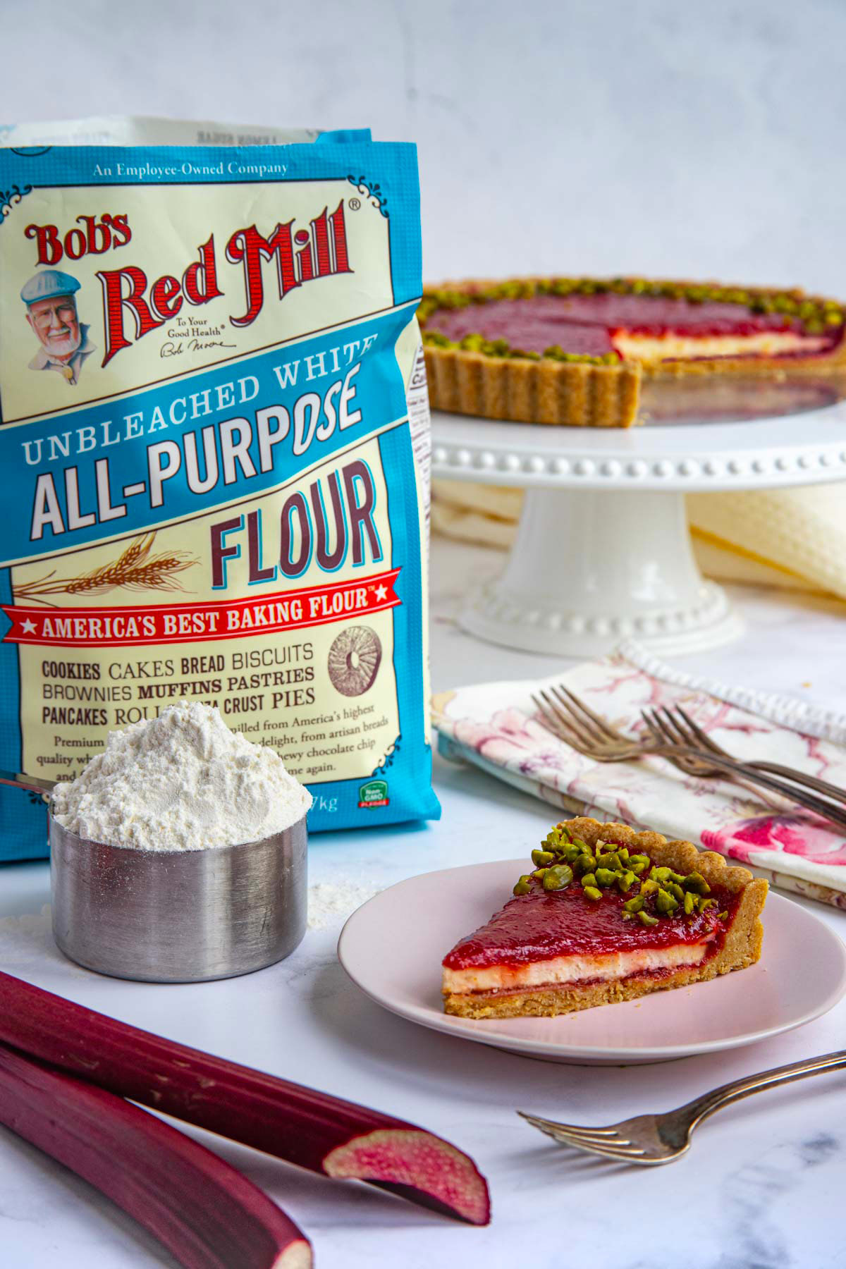 A slice of the rhubarb cream tart on a pink dessert plate next to a bag of Bob's Red Mill AP Flour and a measuring cup with flour.