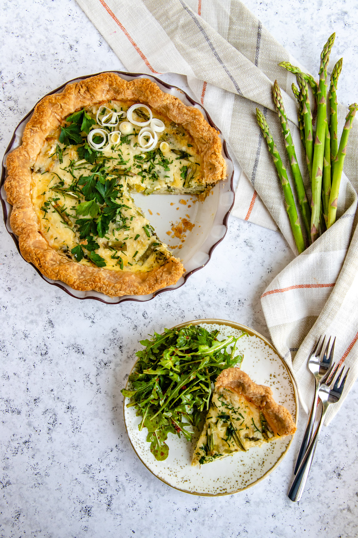 Asparagus and Leek Quiche in a pie plate with a slice on the salad plate with a side salad