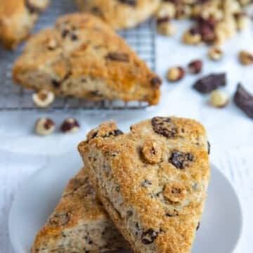 Two chocolate hazelnut scones on a white plate with scones, hazelnuts and chocolate in the background