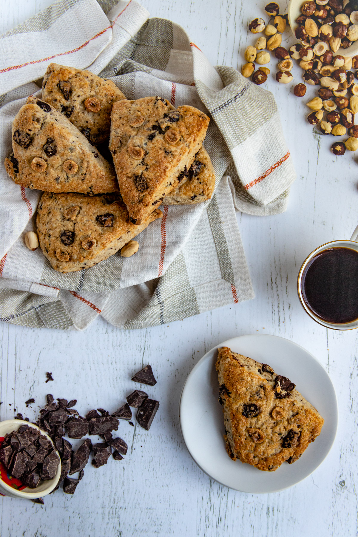 Baked chocolate hazelnut scones in a basket with a scone on a small plate with a cup of coffee and bowls of chopped chocolate and chopped hazelnuts