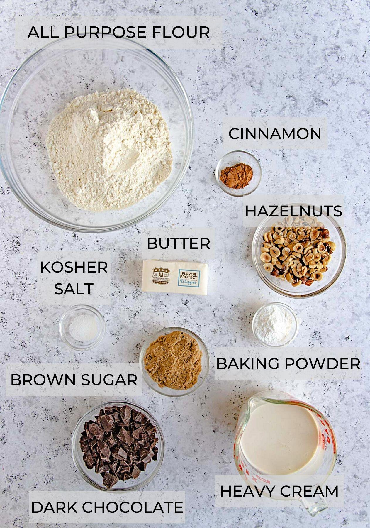 Chocolate hazelnut scone ingredients in separate bowls- flour, hazelnuts, chopped chocolate, heavy cream, brown sugar, butter,  baking powder and kosher salt