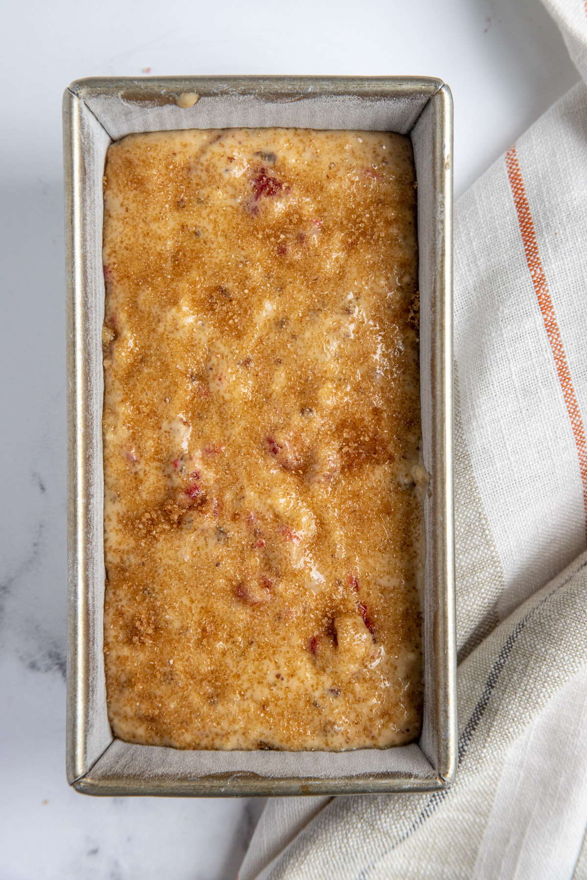 Raspberry Prune Bread Batter scraped into the loaf pan and sprinkled with turbinado sugar