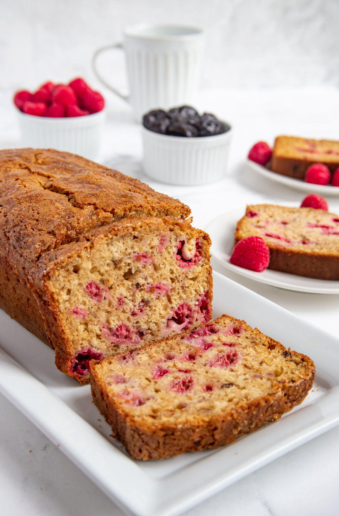 Raspberry Prune Bread on a white platter with prunes and fresh raspberries in the background.