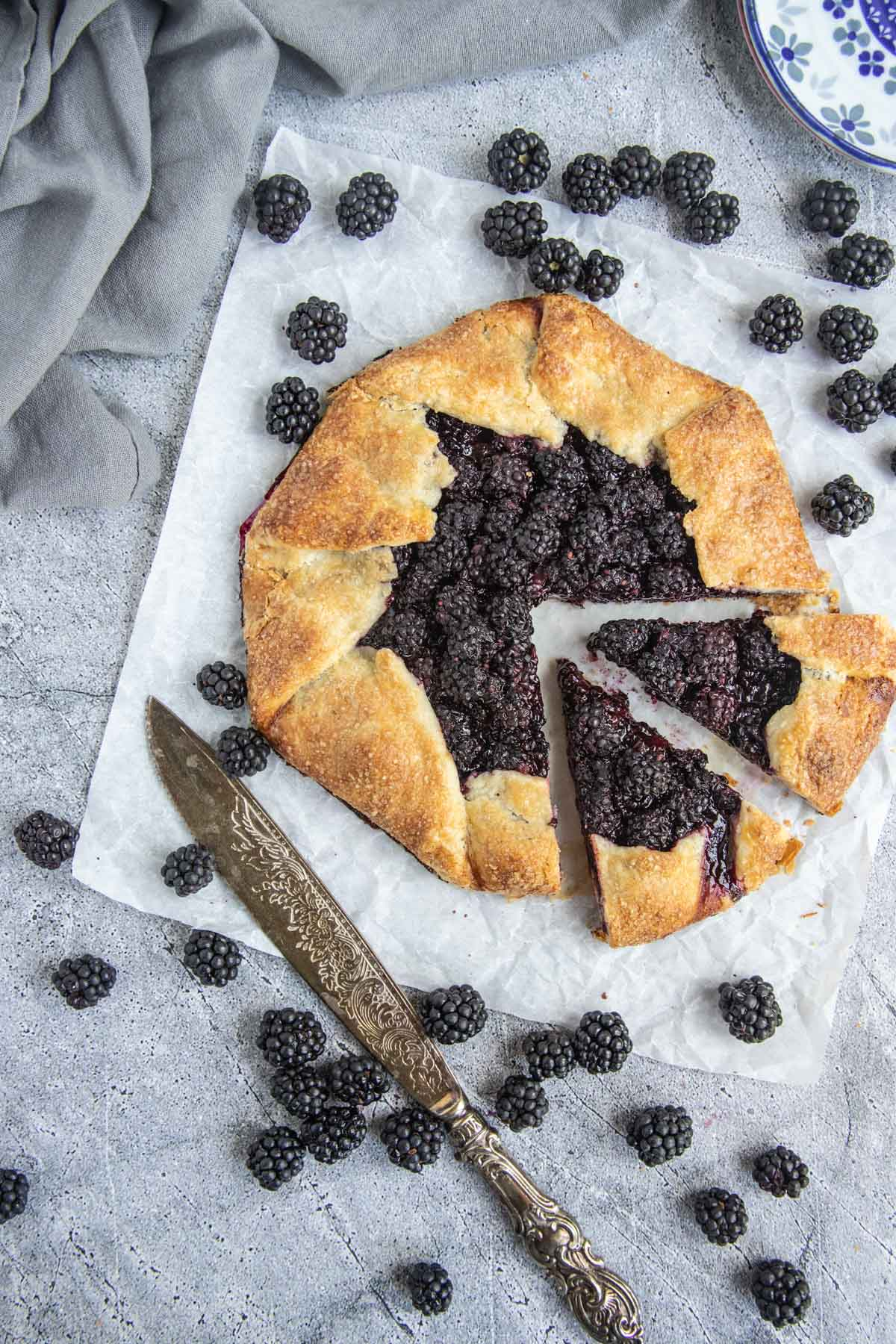 Blackberry Galette on parchment paper and surrounded by fresh blackberries