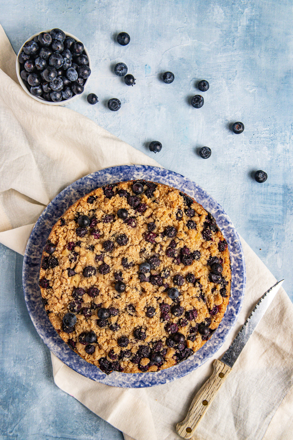 Blueberry Coffee Cake on a blue platter with a bowl of fresh blueberries