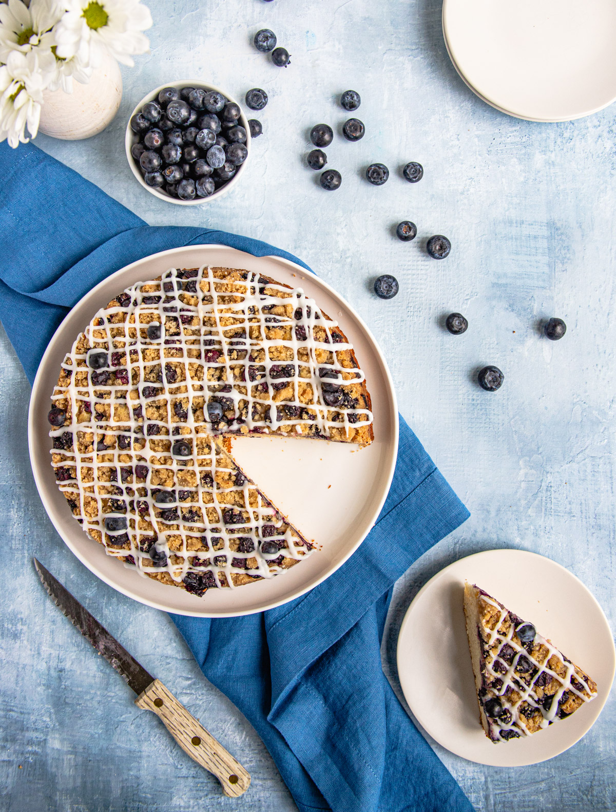 Blueberry Coffee Cake on a blue platter with a bowl of fresh blueberries with a lemon yogurt glaze