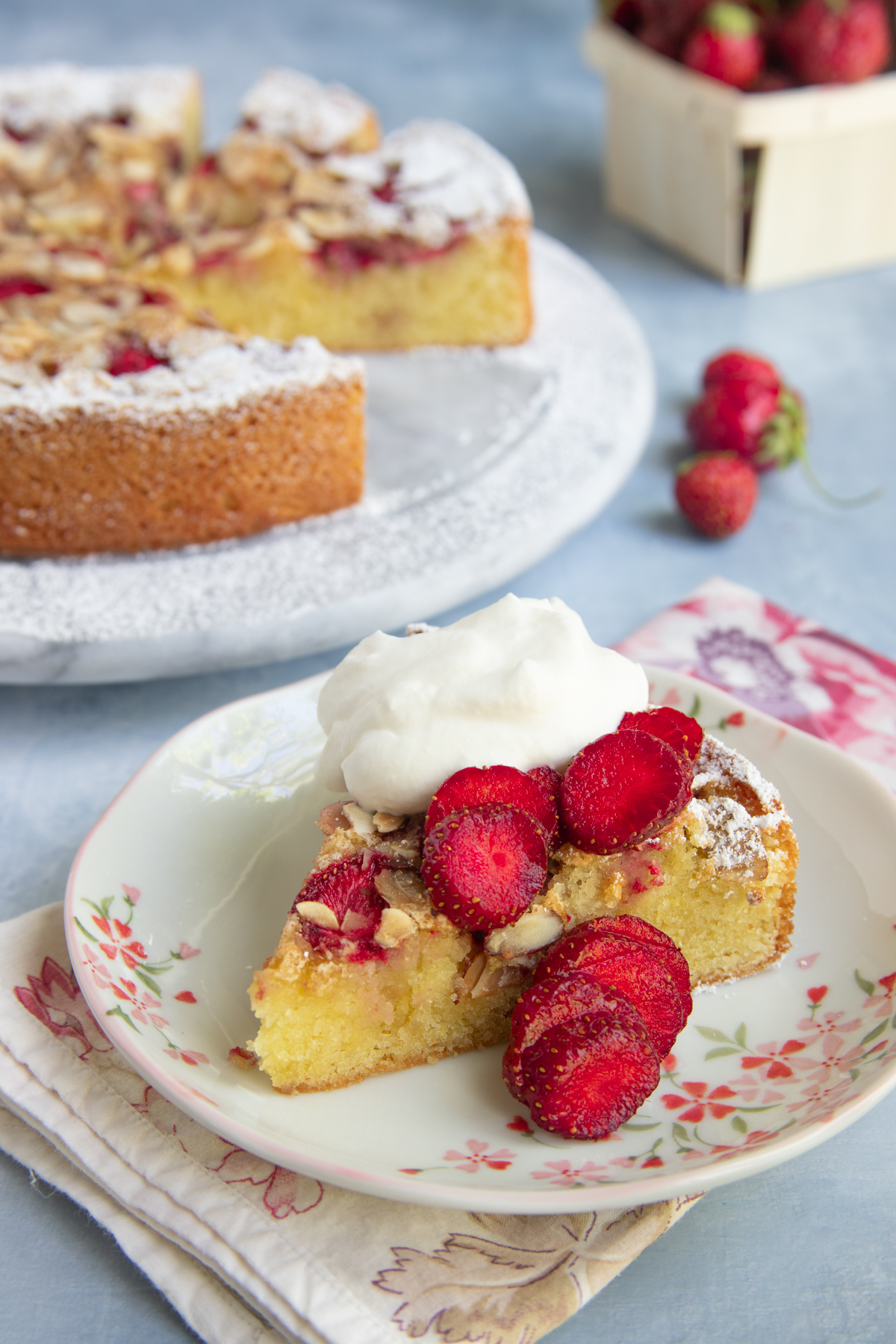 Strawberry Almond Cake slice on dessert plate with whole cake and fresh strawberries  in the background