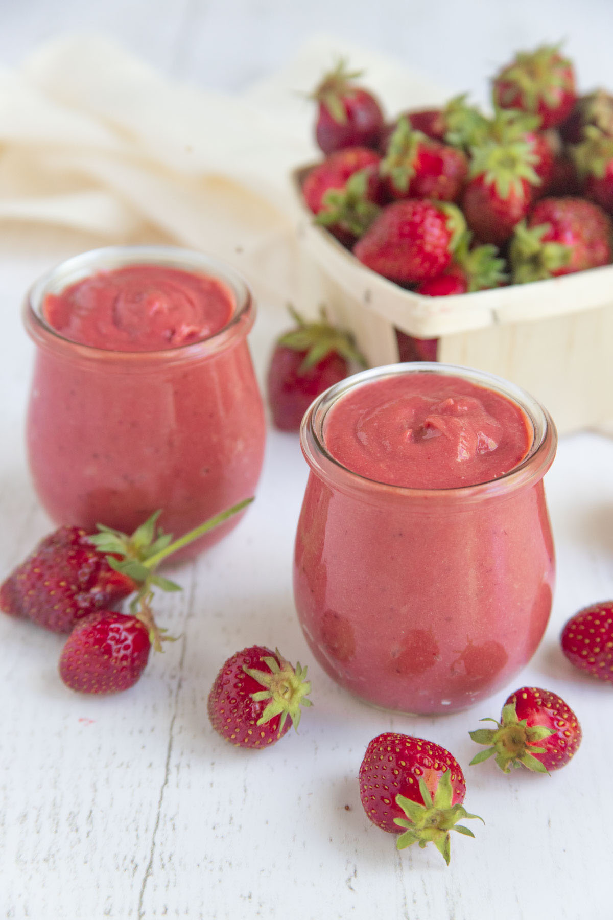 Strawberry curd in two jars with a basket of fresh strawberries