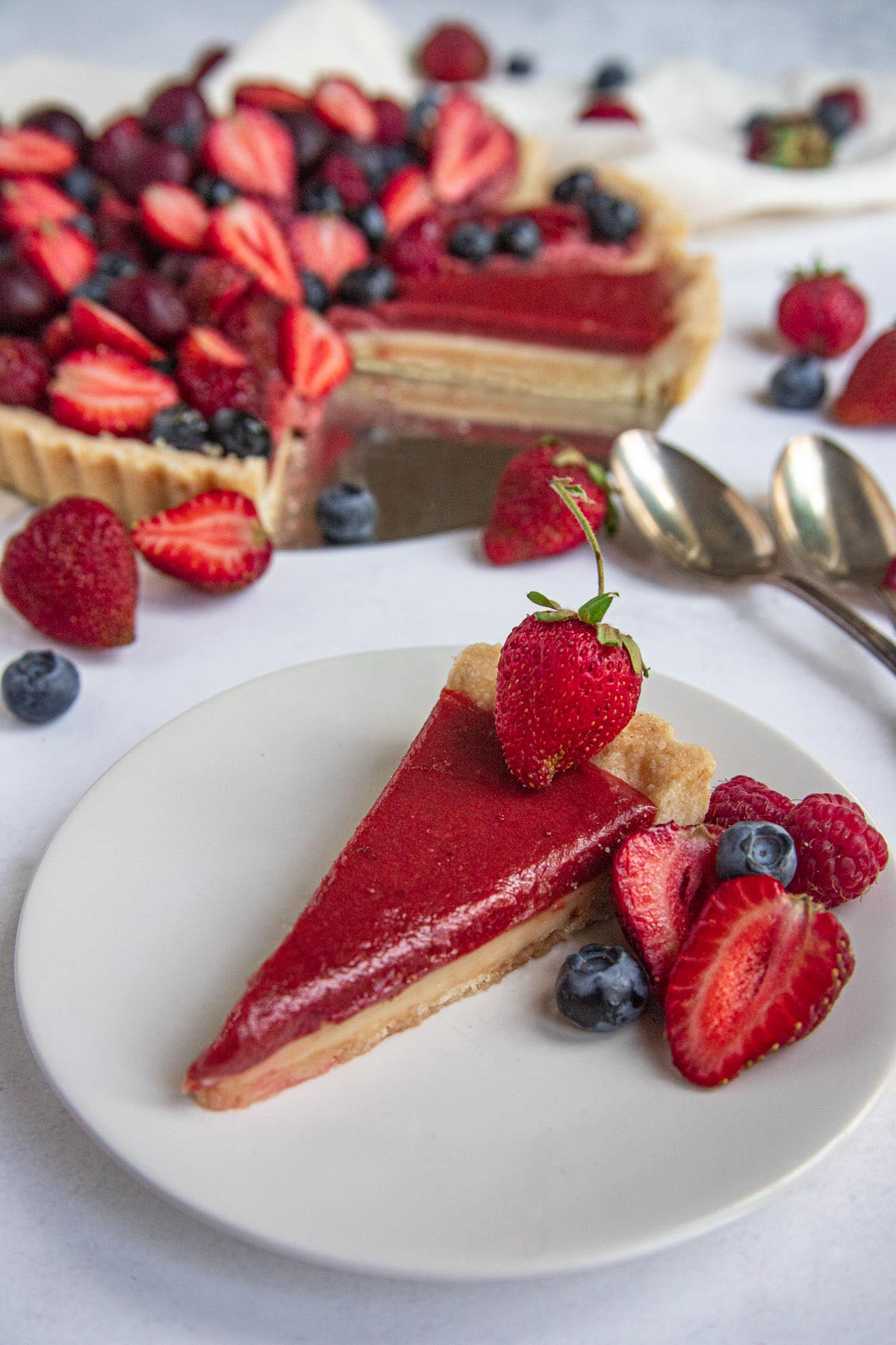 Strawberry and White Chocolate Tart slice on a dessert plate with main tart in the background