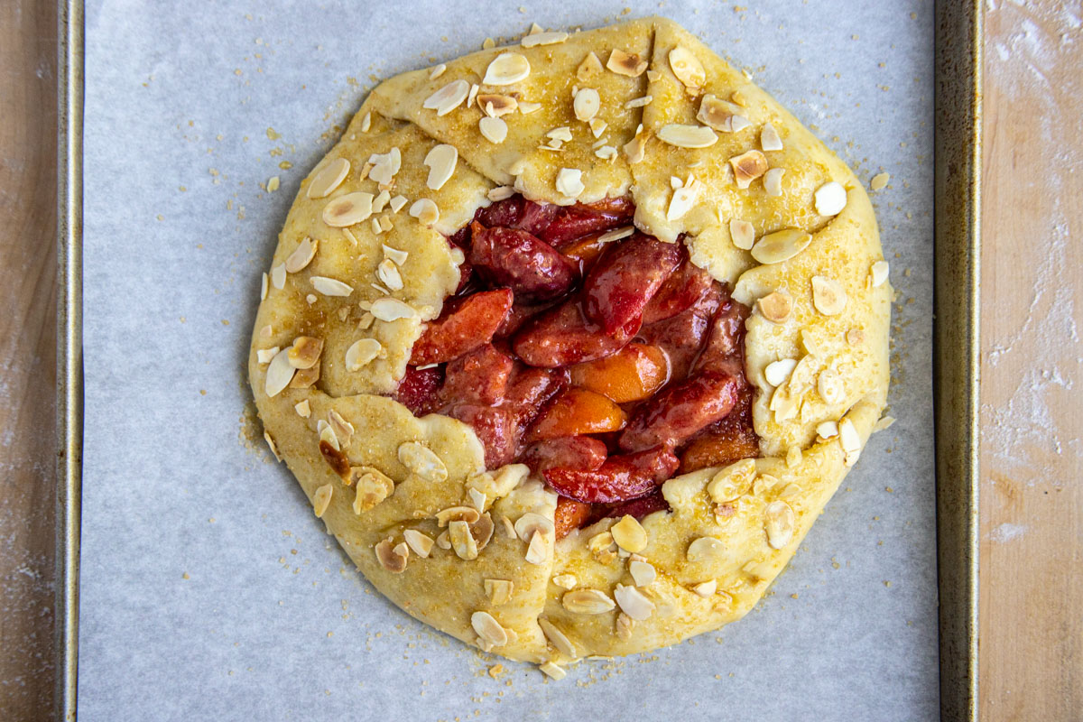 Unbaked apricot and almond galette sprinkled with turbinado sugar and almonds