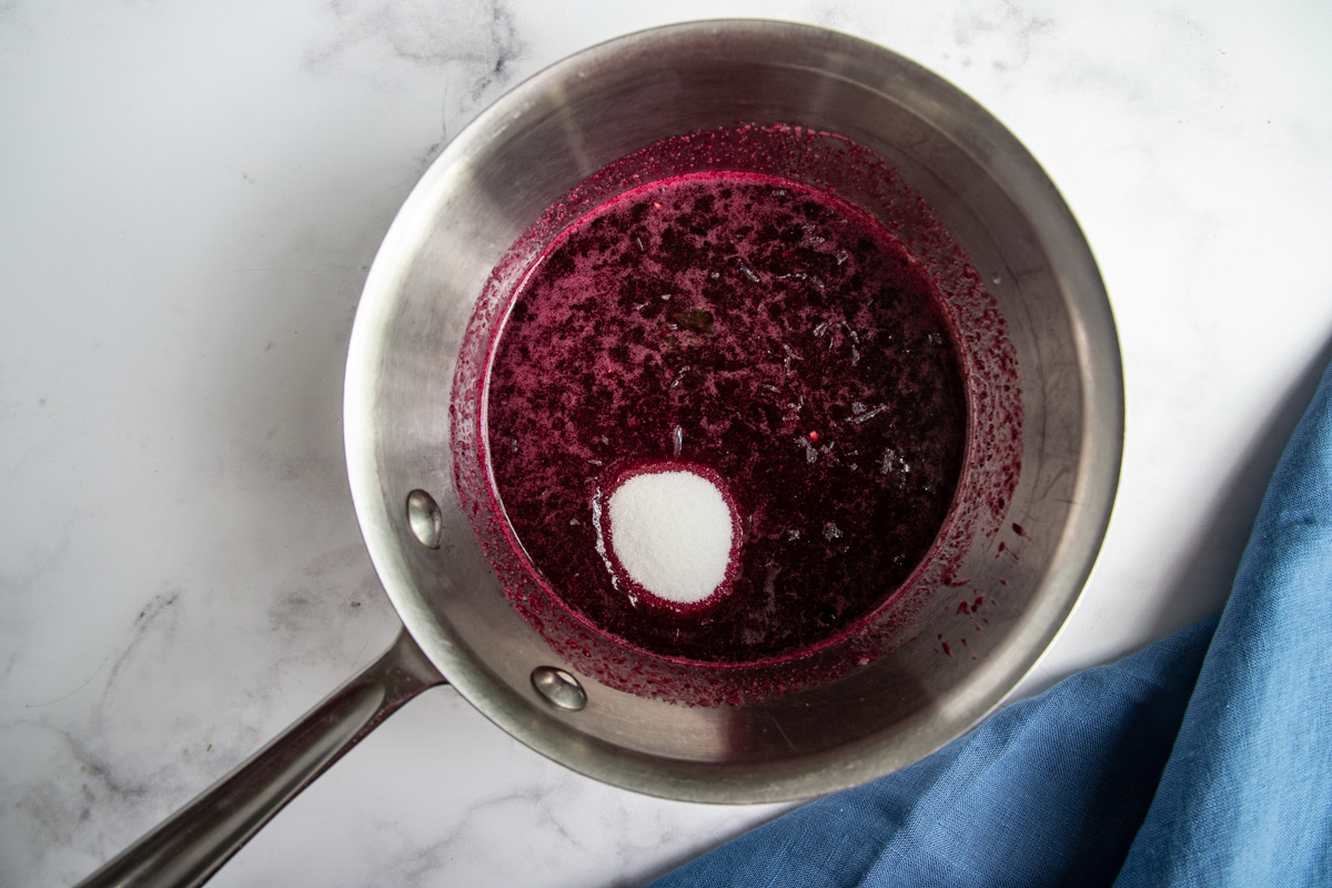 Blueberry puree in saucepan with sugar added