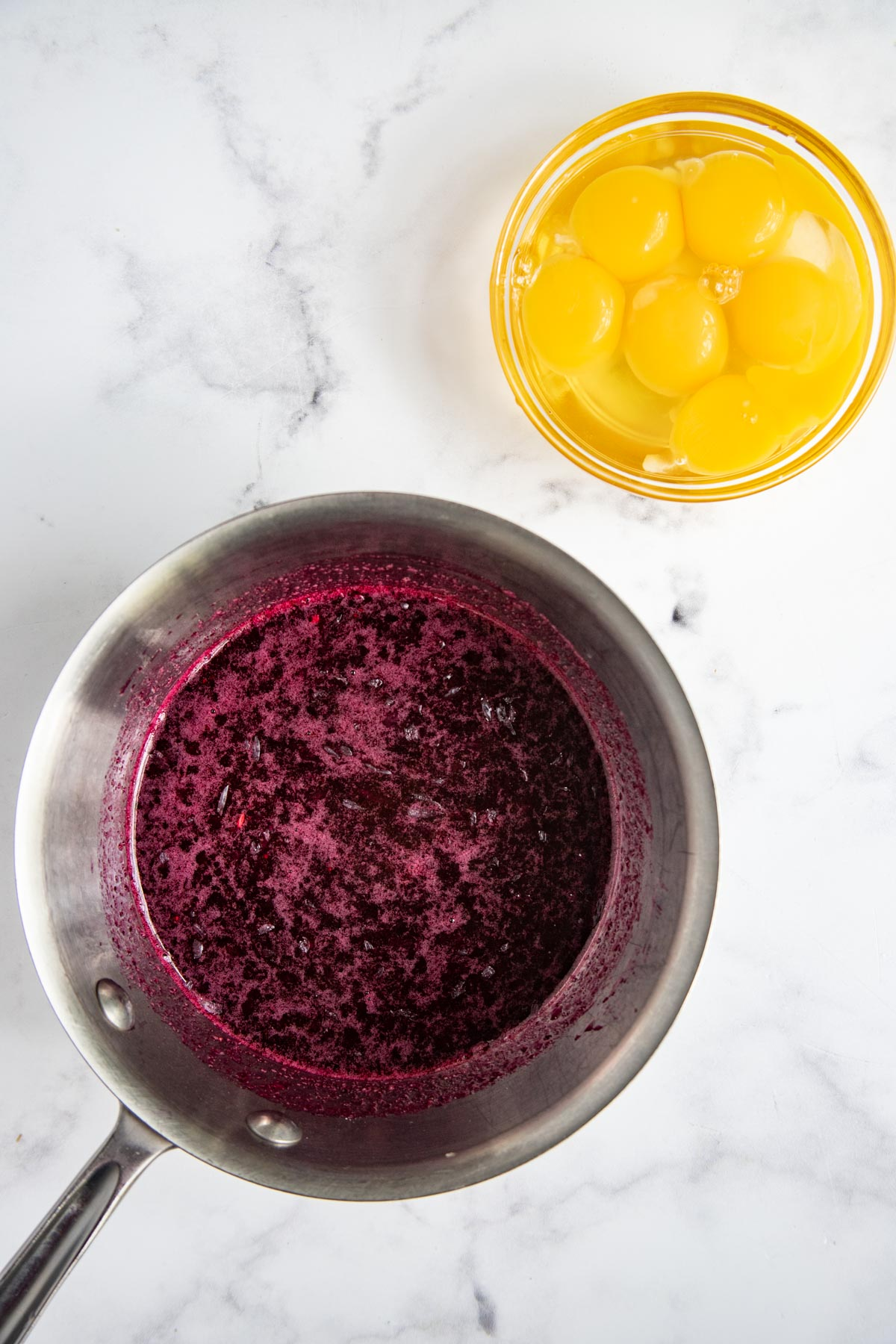 Blueberry puree in a saucepan next to a bowl of eggs