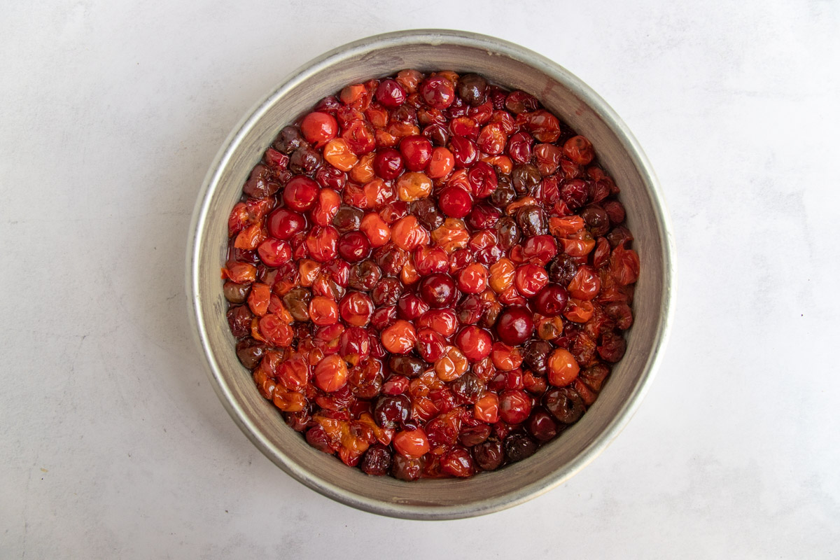Sour cherries placed on bottom of the cake pan.