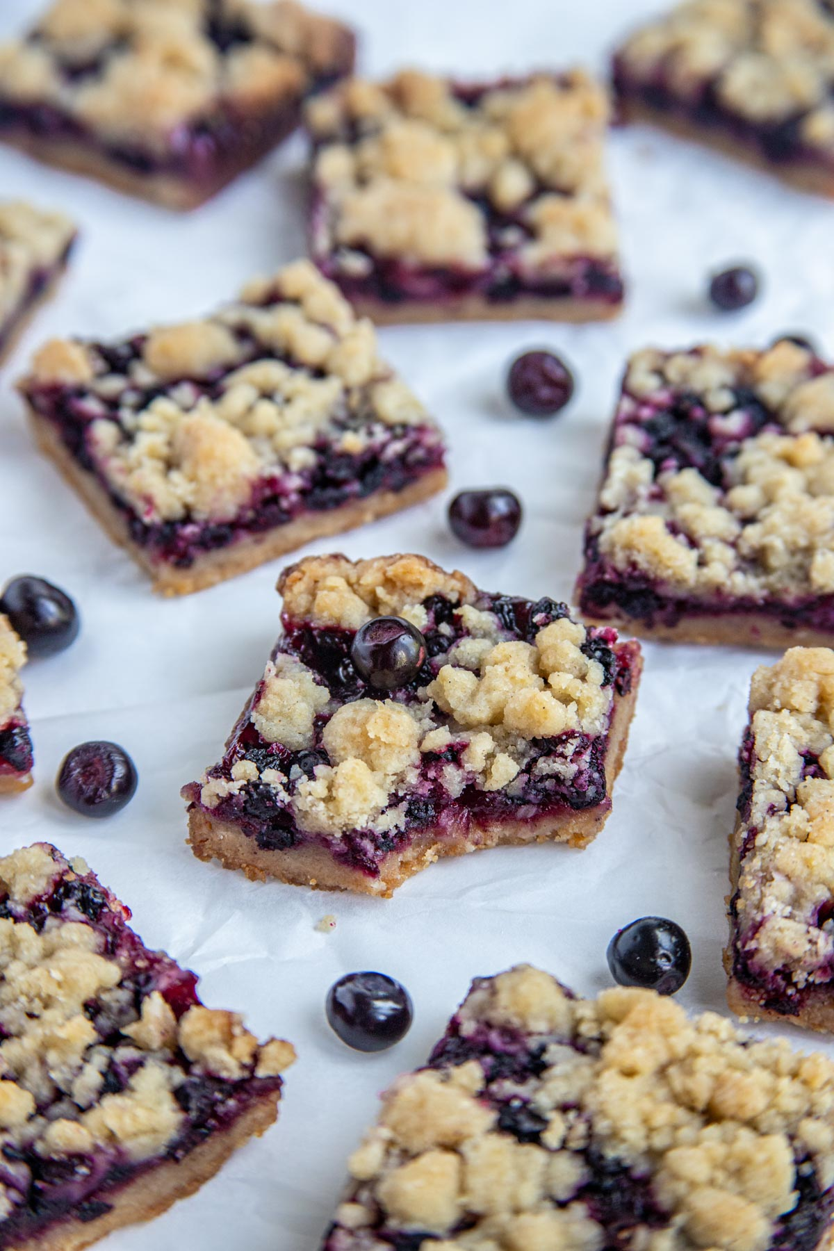 Huckleberry Crumb Bars cut into squares on white parchment paper with fresh huckleberries