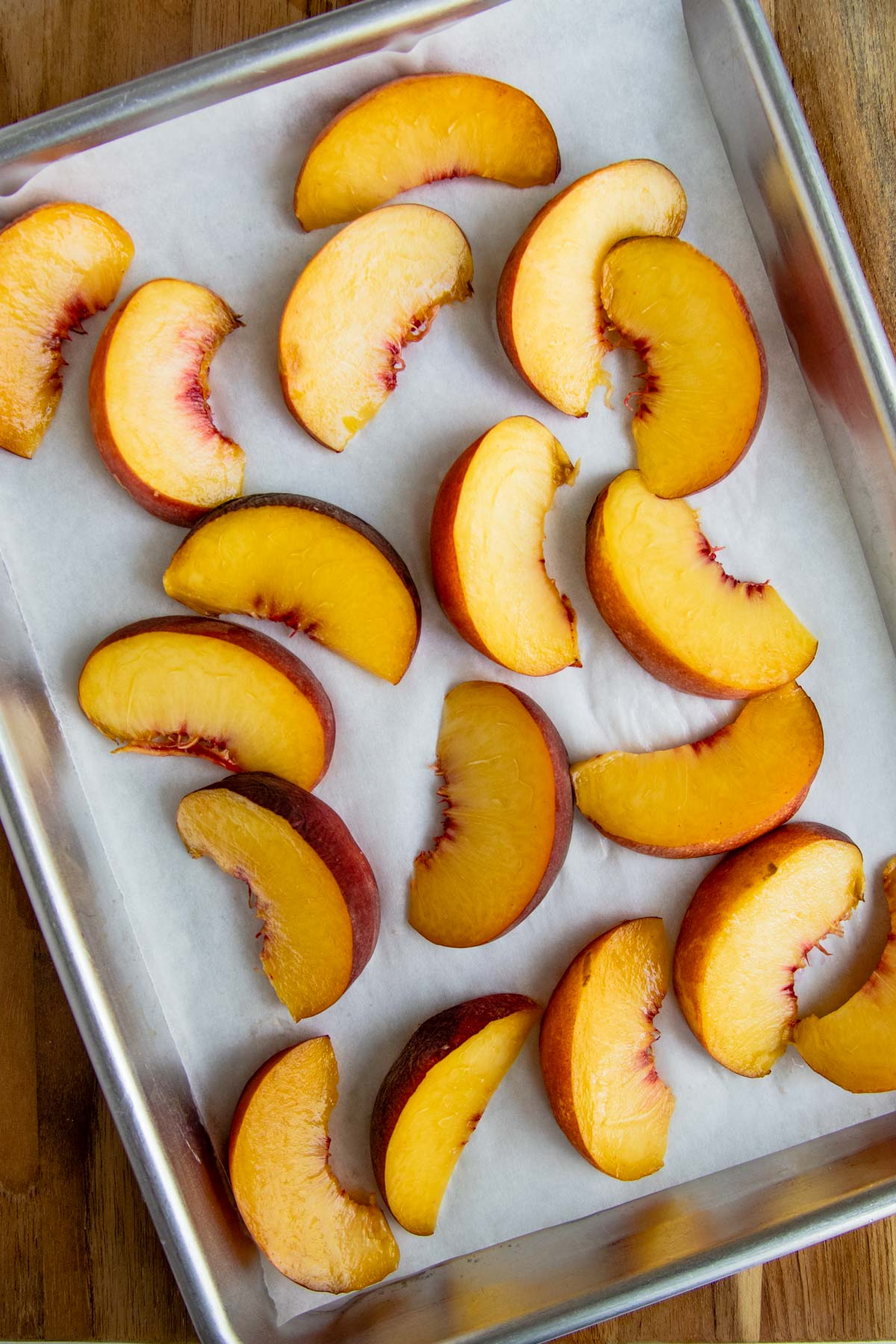 Cut peaches on a parchment lined baking sheet