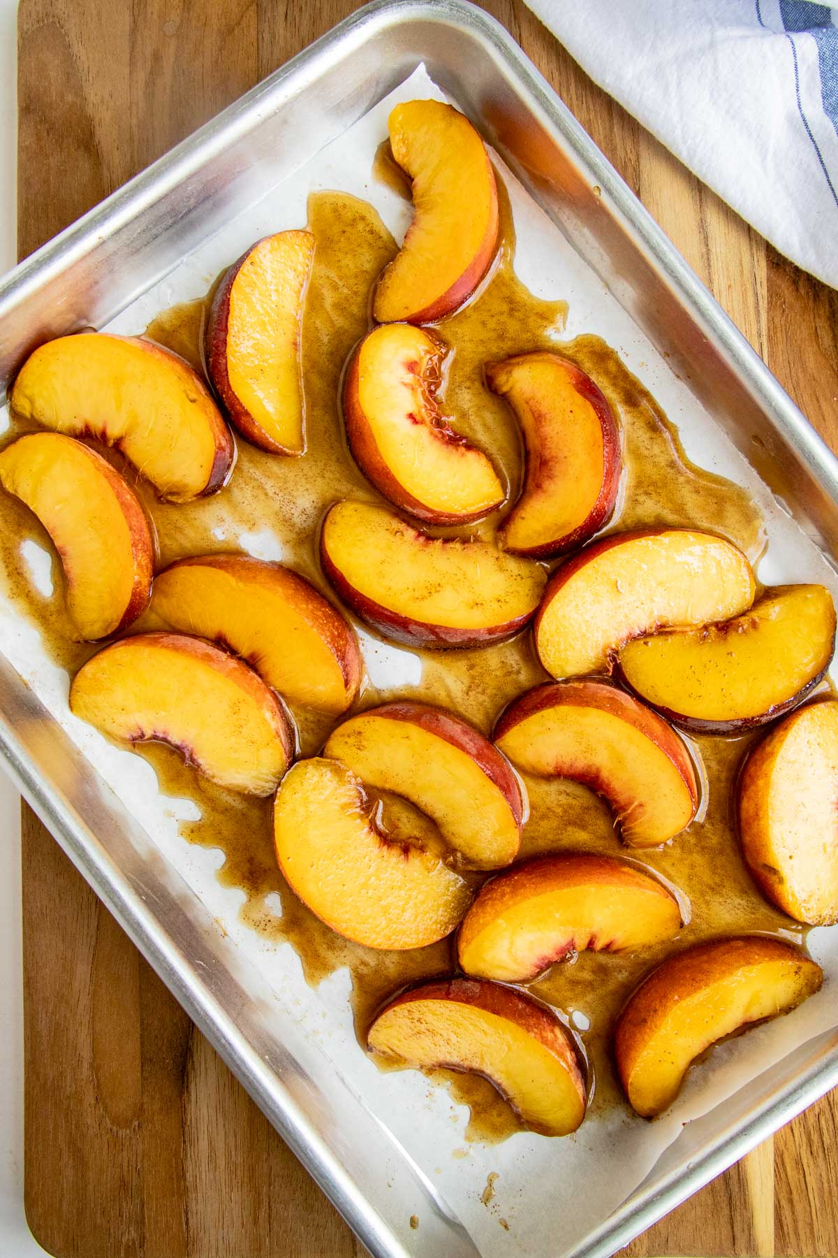 Roasted peaches on a parchment lined baking sheet