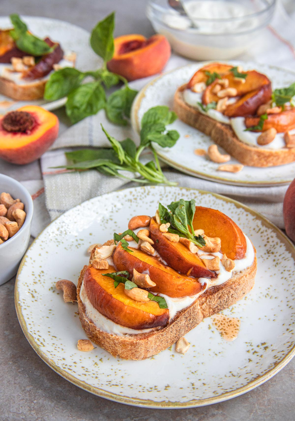 Roasted Peach and Ricotta Tartine on a plate with cashews, peaches and tartine in the background.