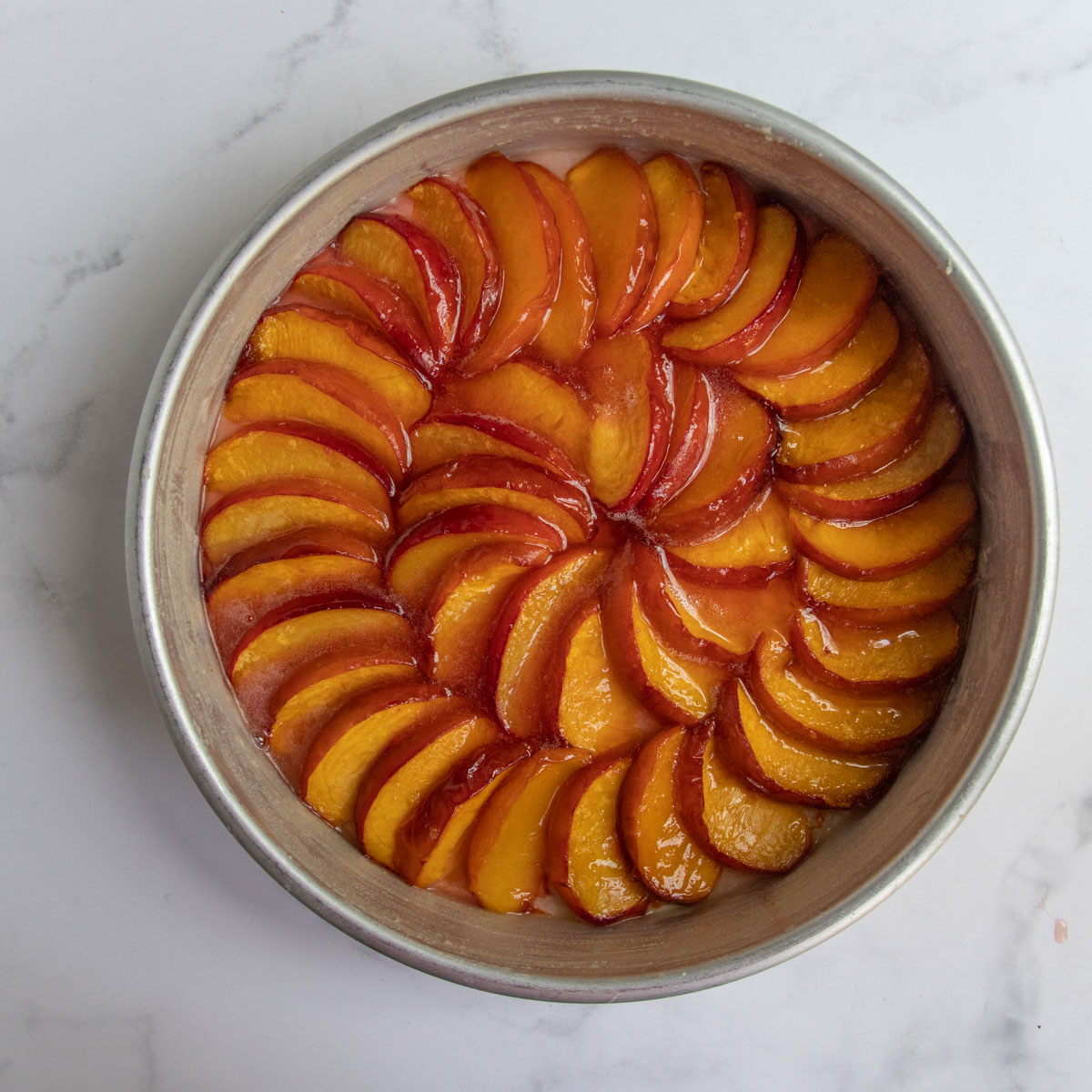 Roasted peaches arranged in a spiral pattern in a cake pan