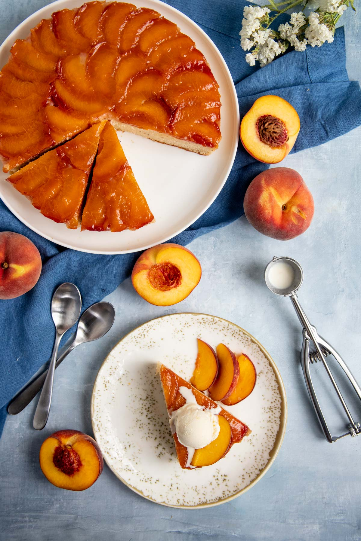 Peach Bourbon Upside Down Cake on a platter next to a slice of cake topped with ice cream.